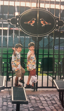 Christopher as a young boy wearing external fixator with cover with his twin at Camden Yards