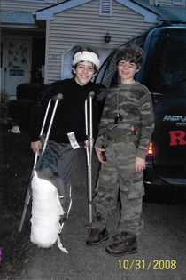 Christopher as a boy on crutches wearing external fixator covered in bandages as part of military Halloween costume with his twin