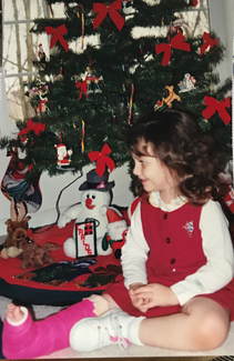 Katia as a young girl in a cast by a Christmas tree