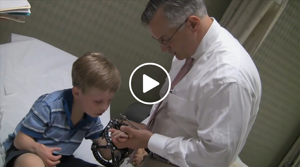 Dr. Shawn Standard checking the hand of a boy patient who is wearing an external fixator on his arm in the International Center for Limb Lengthening clinic