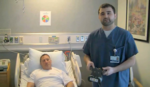 Picture from the video of research program coordinator holding the external remote control of a PRECICE internal lengthening system by the hospital bed of a male patient
