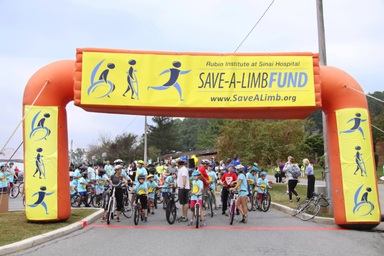 Crowd of bike riders behind Save-A-Limb Fund inflatable starting line at Rubin Institute for Advanced Orthopedics 2016 Save-A-Limb Fund Event