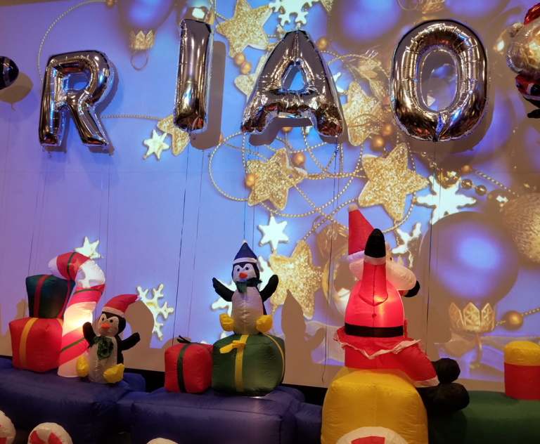 Inflatable train with Santa and penguins with gifts and balloons spelling out RIAO (Rubin Institute for Advanced Orthopedics) at the International Center for Limb Lengthening pediatric holiday party