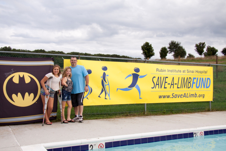 A father poses with 2 young girl patients, one using crutches, in front of Batman and Save-A-Limb Fund banners at Rubin Institute for Advanced Orthopedics 2018 Save-A-Limb Pool Party event