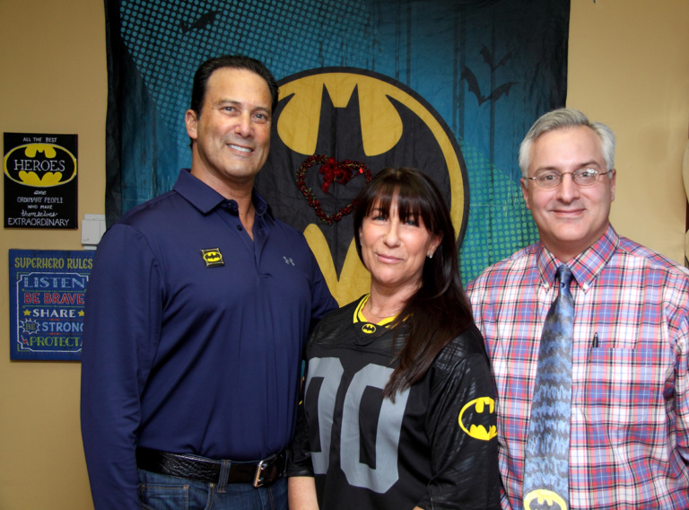 "Dr. Shawn Standard poses with the family of Leonard B. ""Batman"" Robinson in front of Batman banner at the International Center for Limb Lengthening's Leonard B. ""Batman"" Robinson Memorial Valentine's Day Party"