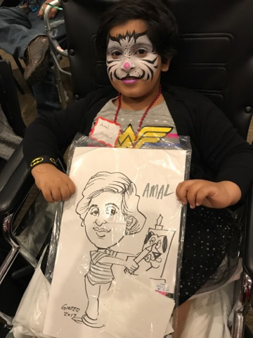 Young child in wheelchair with face painted holds up her caricature at the International Center for Limb Lengthening pediatric holiday party