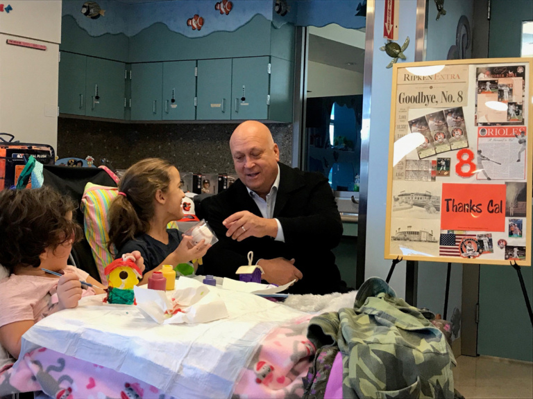 Cal Ripken gives baseball to young girl patient in wheelchair at Cal Ripken at Herman & Walter Samuelson Children