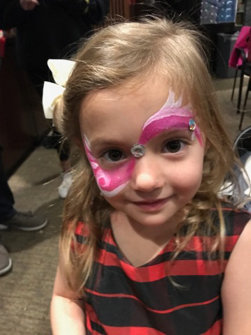 Young girl with pink face painting at the International Center for Limb Lengthening pediatric holiday party