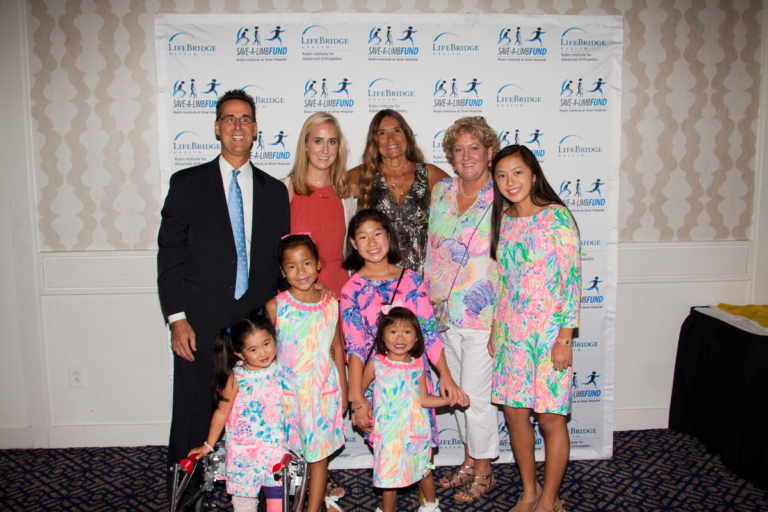Pediatric Liaison Marilyn Richardson poses with family with 5 girls in matching pastel floral dresses at Rubin Institute for Advanced Orthopedics 2017 Save-A-Limb Fund Dinner