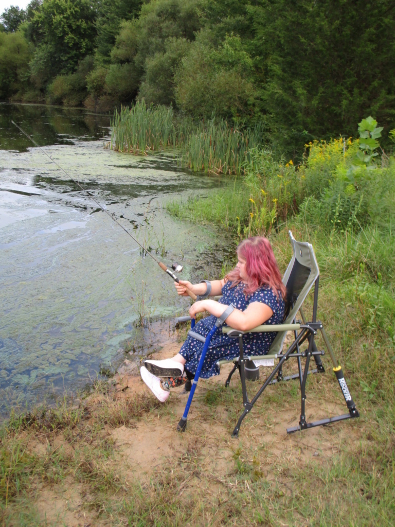Girl with forearm crutches sitting in chair fishing at pond during Rubin Institute for Advanced Orthopedics 2018 Save-A-Limb Pool Party event