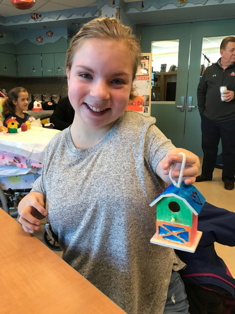Girl patient shows off painted birdhouse at Herman & Walter Samuelson Children