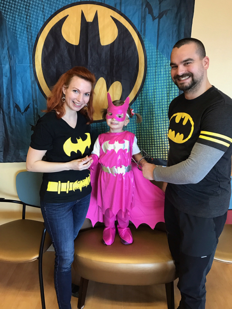 "Mother and father in Batman shirts holding hands of young girl wearing an external fixator on one arm and dressed in a pink Batgirl costume take photo in front of Batman banner at the International Center for Limb Lengthening's Leonard B. ""Batman"" Robinson Memorial Valentine's Day Party"