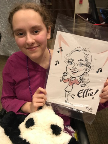 Girl holds up her caricature at the International Center for Limb Lengthening pediatric holiday party