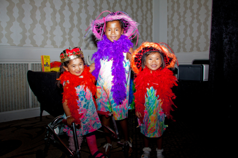 3 young girls, one using a walker, dress up in bright boas and hats for the photo booth at Rubin Institute for Advanced Orthopedics 2017 Save-A-Limb Fund Dinner