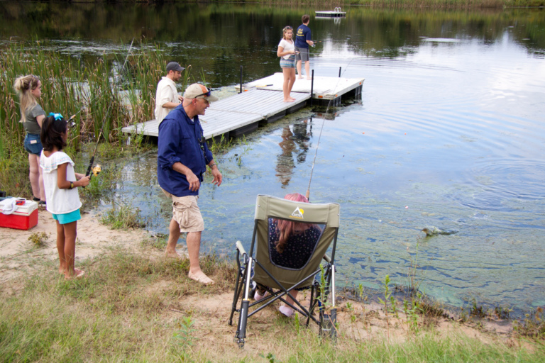 Dr. Shawn Standard fishing with patients and children at pond during Rubin Institute for Advanced Orthopedics 2018 Save-A-Limb Pool Party event