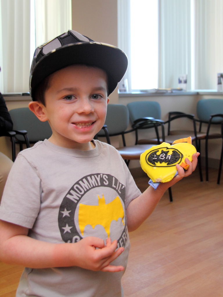 "Young boy in Batman shirt holds Batman cookie at the International Center for Limb Lengthening's Leonard B. ""Batman"" Robinson Memorial Valentine's Day Party"