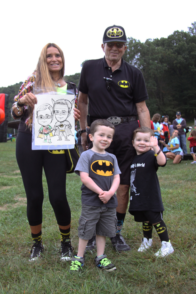 Pediatric Liaison Marilyn Richardson poses with 1 male adult and 2 young boys all wearing Batman gear while holding a Batman and Robin caricature of the boys at Rubin Institute for Advanced Orthopedics 2016 Save-A-Limb Fund Event