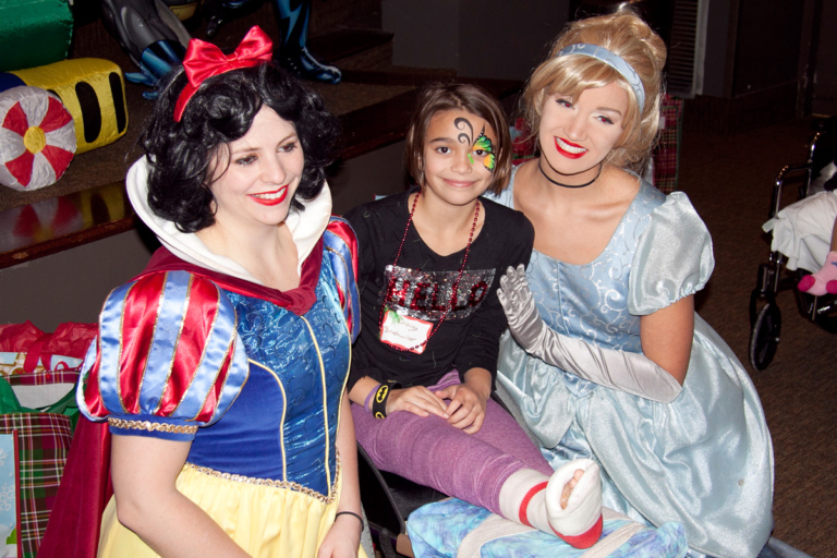 Girl patient in leg cast poses with Snow White and Cinderella at the International Center for Limb Lengthening pediatric holiday party