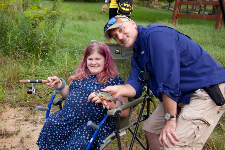 Dr. Shawn Standard poses with girl with forearm crutches showing caught fish at Rubin Institute for Advanced Orthopedics 2018 Save-A-Limb Pool Party event