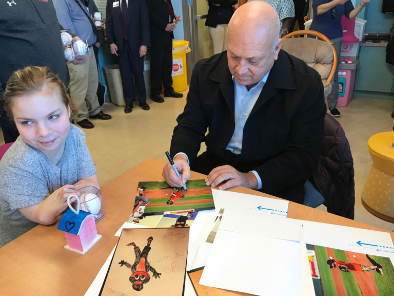 Cal Ripken autographs photo for girl patient at Cal Ripken at Herman & Walter Samuelson Children