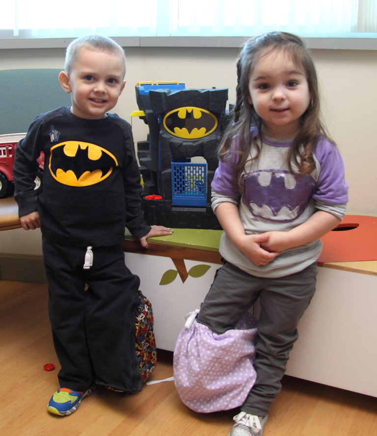 "One young girl and one young boy both wearing Batman shirts and with covered external fixators on opposite legs play with a Batman toy at the International Center for Limb Lengthening's Leonard B. ""Batman"" Robinson Memorial Valentine's Day Party"