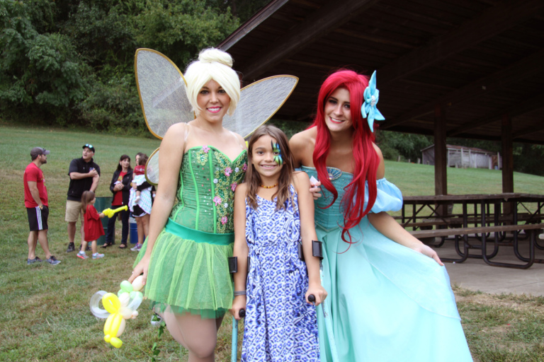 Young girls with facepaint and forearm crutches poses with Tinker Bell and the Little Mermaid at Rubin Institute for Advanced Orthopedics 2016 Save-A-Limb Fund Event