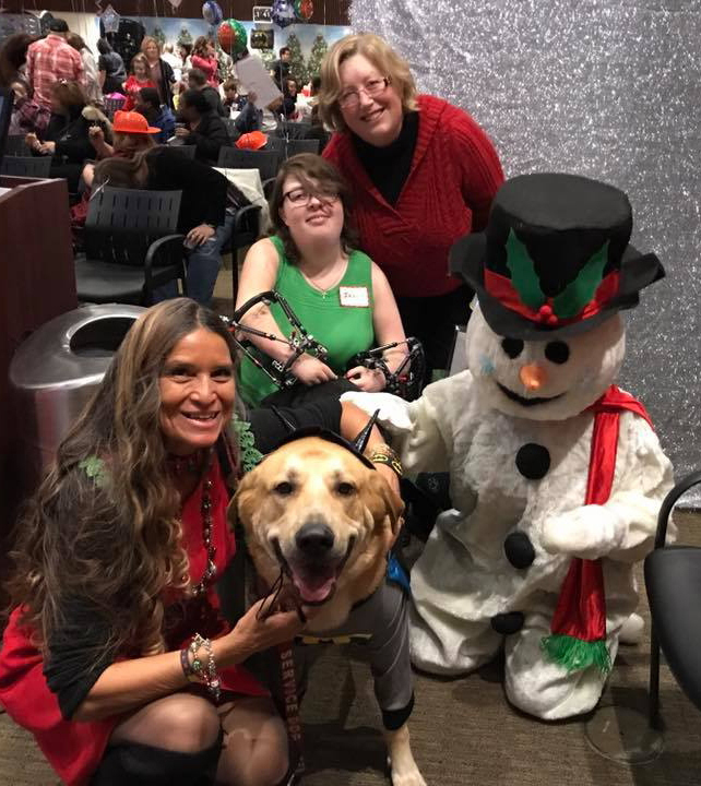Pediatric Liaison Marilyn Richardson poses with girl patient with external fixators on both arms, mother, service dog, and Frosty the Snowman at the International Center for Limb Lengthening pediatric holiday party