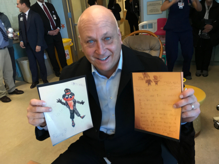 Cal Ripken holds up children's artwork at Cal Ripken at Herman & Walter Samuelson Children