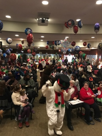 Frosty the Snowman, Rudolph and Santa work their way through an aisle between the seated crowd at the International Center for Limb Lengthening pediatric holiday party
