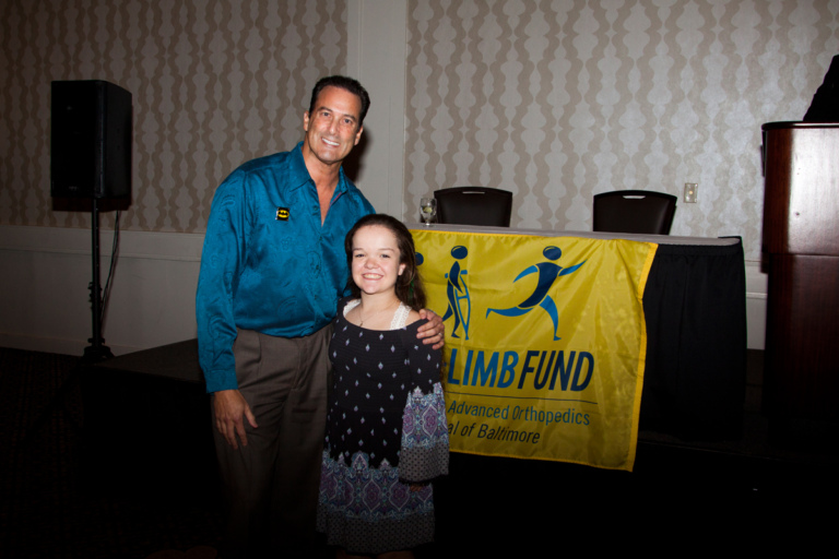 "Family member of Leonard B. ""Batman"" Robinson with female patient in front of Save-A-Limb Fund banner at Rubin Institute for Advanced Orthopedics 2017 Save-A-Limb Fund Dinner"