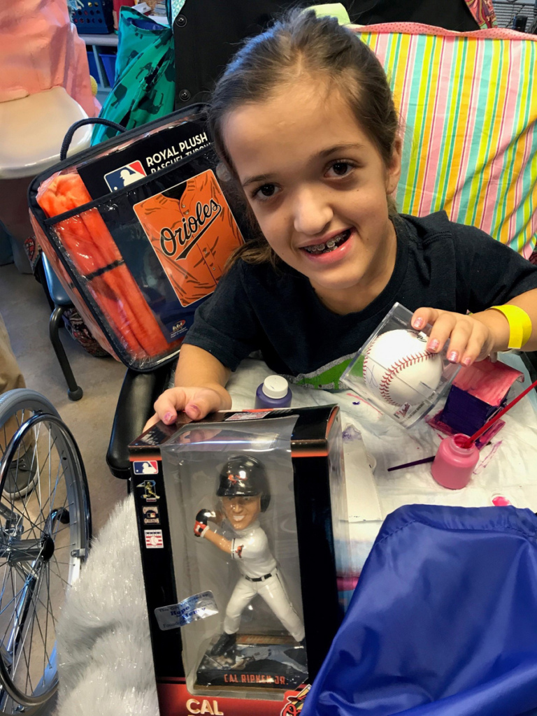 Young girl patient in wheelchair with baseball, blanket, and bobble head at Herman & Walter Samuelson Children
