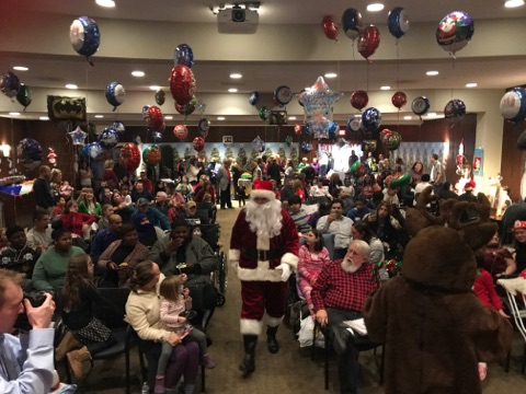 Santa walking through an aisle between the seated crowd at the International Center for Limb Lengthening pediatric holiday party