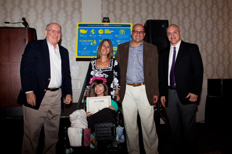 Dr. John Herzenberg and Dr. Shawn Standard present an award to a young girl in a wheelchair and her parents at Rubin Institute for Advanced Orthopedics 2017 Save-A-Limb Fund Dinner
