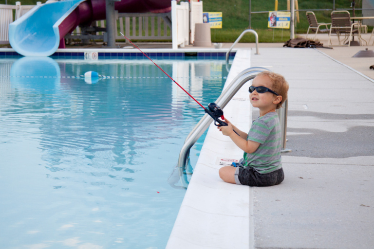 Young boy fishing in swimming pool at Rubin Institute for Advanced Orthopedics 2018 Save-A-Limb Pool Party event