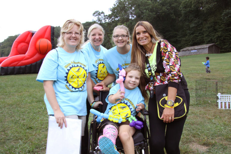 Pediatric Liaison Marilyn Richardson poses for a picture with a young girl in a cast in a wheelchair holding balloon animals and 3 participants at Rubin Institute for Advanced Orthopedics 2016 Save-A-Limb Fund Event