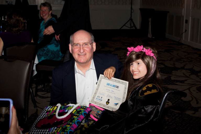 Dr. John Herzenberg with young girl in wheelchair with award at Rubin Institute for Advanced Orthopedics 2017 Save-A-Limb Fund Dinner