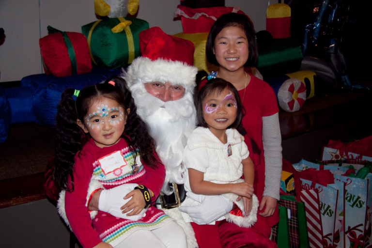 3 young girls take photo with Santa at the International Center for Limb Lengthening pediatric holiday party