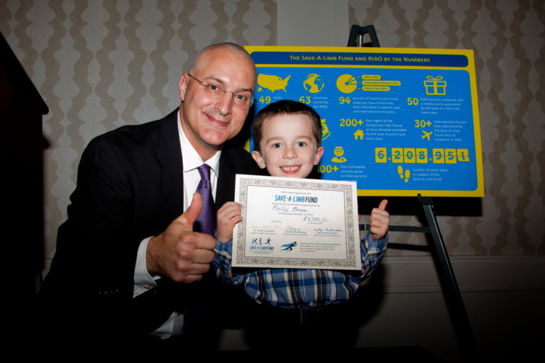 Dr. Shawn Standard and young boy with award both give a thumbs up at Rubin Institute for Advanced Orthopedics 2017 Save-A-Limb Fund Dinner