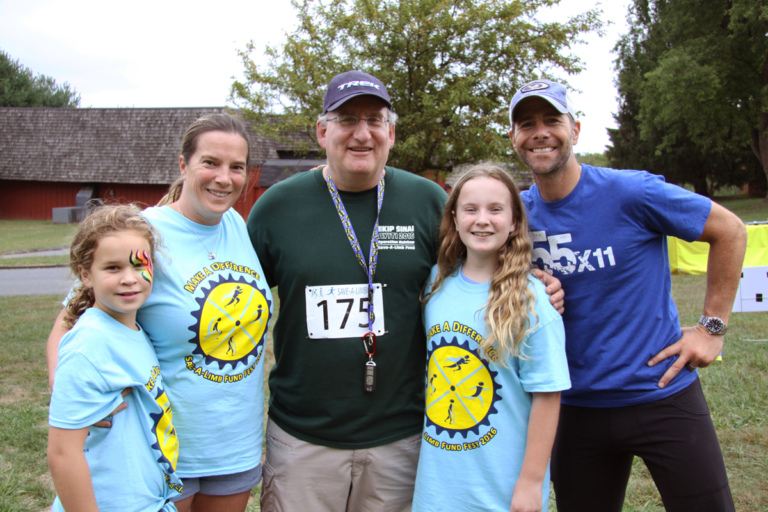 Dr. John Herzenberg posing for a photo with 2 young girls, woman, and man at Rubin Institute for Advanced Orthopedics 2016 Save-A-Limb Fund Event