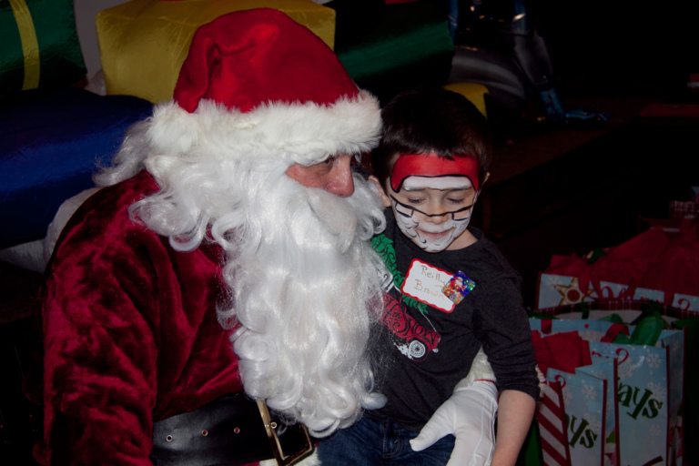 Young boy with Santa face painting sits on Santa's lap at the International Center for Limb Lengthening pediatric holiday party
