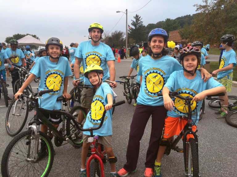 2 adults and 3 children in Save-A-Limb blue event shirts on bikes at Rubin Institute for Advanced Orthopedics 2016 Save-A-Limb Fund Event