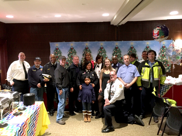 Pediatric Liaison Marilyn Richardson poses with firemen and volunteers at the International Center for Limb Lengthening pediatric holiday party