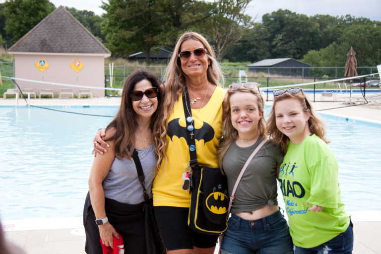 Marilyn Richardson, Pediatric Liaison, Merrill Herzenberg, and 2 female patients pose for photo at Rubin Institute for Advanced Orthopedics 2018 Save-A-Limb Pool Party event