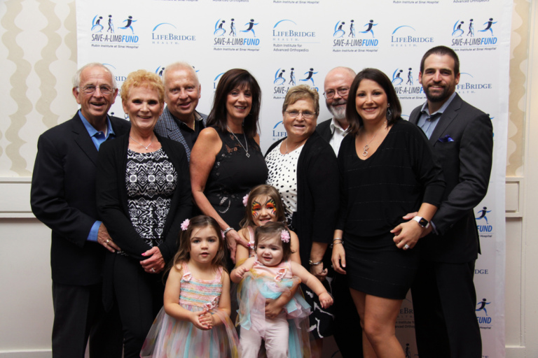 8 adult guests with 3 young girls all wearing pastel dresses standing in front of Save-A-Limb Fund photo backdrop at Rubin Institute for Advanced Orthopedics 2016 Save-A-Limb Fund Dinner