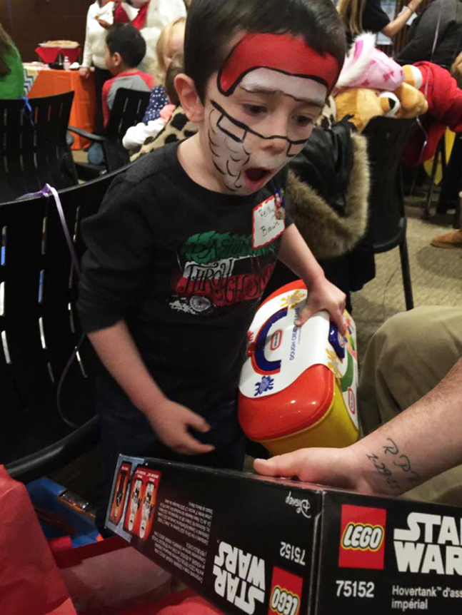 Young boy with Santa face painting has his mouth open wide with excitement in looking at presents at the International Center for Limb Lengthening pediatric holiday party