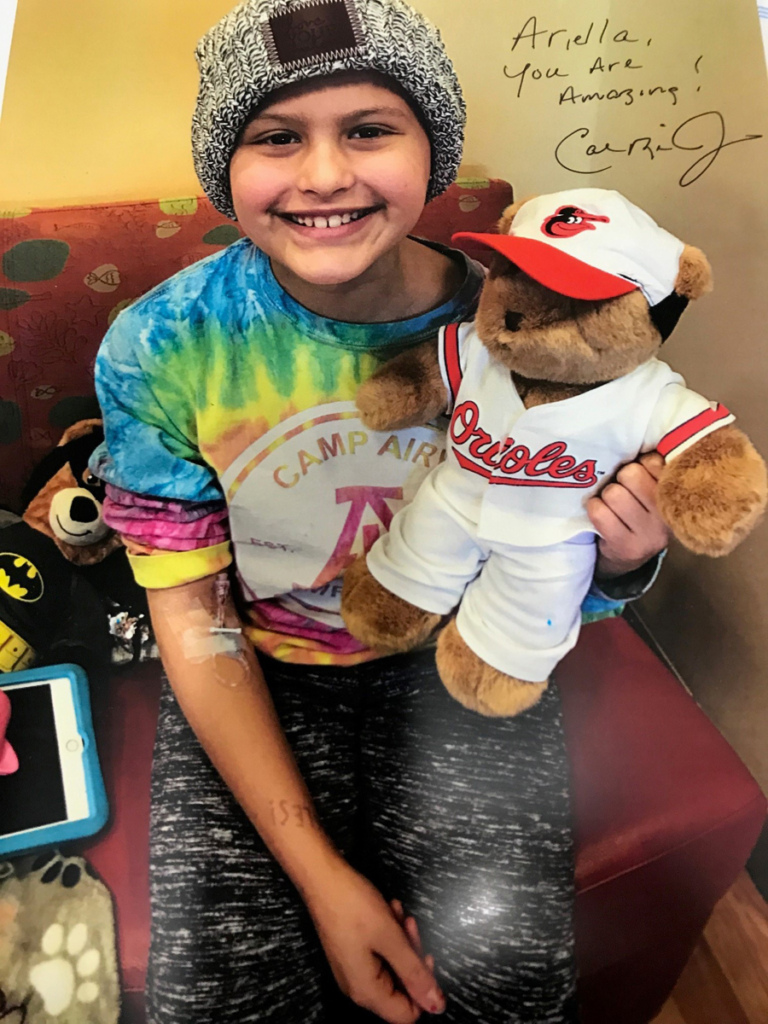Cal Ripken autographed picture of girl patient holding Baltimore Orioles teddy bear