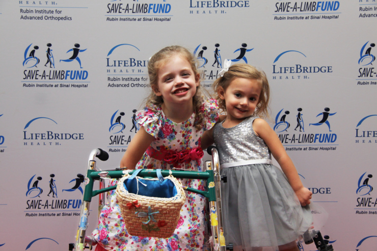2 young girls in dresses, one with a walker standing in front of Save-A-Limb Fund photo backdrop at Rubin Institute for Advanced Orthopedics 2016 Save-A-Limb Fund Dinner