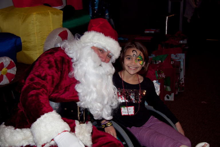 Young girl with face paint in wheelchair with cast takes picture with Santa at the International Center for Limb Lengthening pediatric holiday party