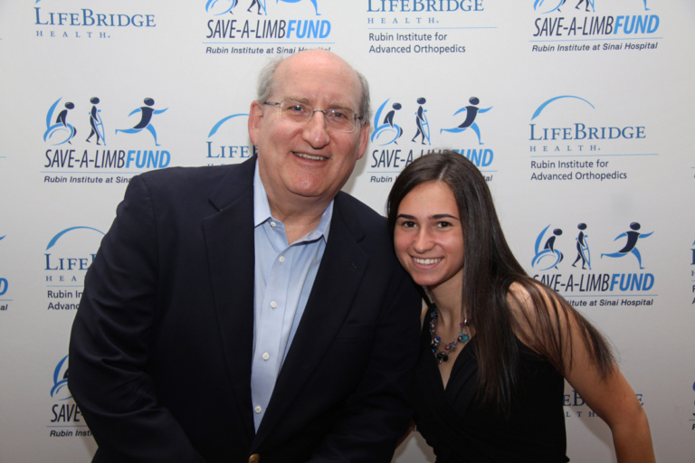 Dr. John Herzenberg and girl in front of Save-A-Limb Fund photo backdrop at Rubin Institute for Advanced Orthopedics 2016 Save-A-Limb Fund Dinner
