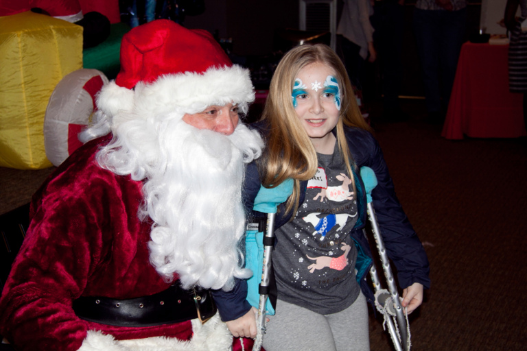 Young girl with crutches and face paint takes picture with Santa at the International Center for Limb Lengthening pediatric holiday party